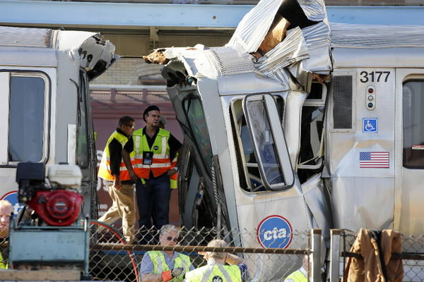 Officials examine damage of an out-of-service CTA train, right, that ran head-on into a a stopped train at a Blue Line station in Forest Park on Monday, sending dozens of people to hospitals in Forest Park.