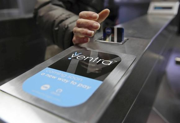 A CTA turnstile promotes the coming Ventra fare card system. The card's debit account option has sparked criticsim over its various fees.