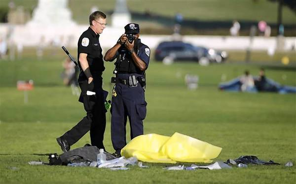 Police officers investigate the scene where a man set himself on fire in front of the U.S. Capitol building.