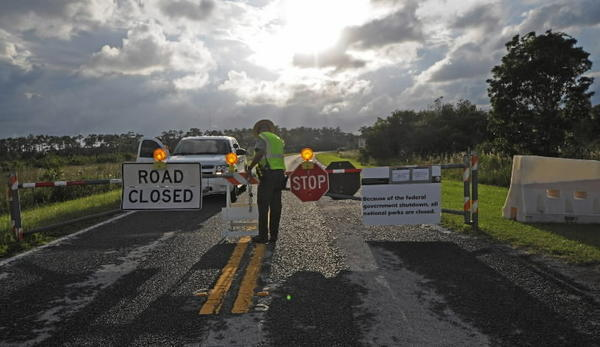 Because of the government shutdown a federal law enforcement ranger at Everglades National Park, closes the main gate at 6 p.m., on Tuesday, October 1, 2013.