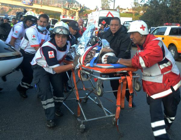 Rescue workers move an injured person at the site where a bus plunged into a ravine along the highway linking the Mexico City suburb of Naucalpan with Toluca.