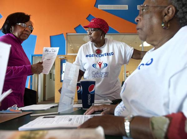 Virginia Owens (center) and Margaret Wilson (right) direct people at the entrance of Enrollfest, an event organized by Celebrate HEALTHCARE to enroll people in the new state health insurance marketplace.