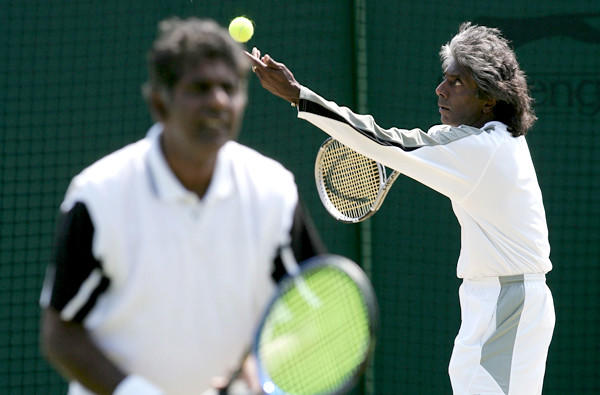 Anand Amritraj prepares to serves as his brother, Vijay, waits at the net during a Wimbledon doubles match.
