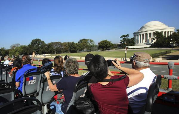 Tourists take pictures of the closed Jefferson Memorial (R) in Washington atop a Big Bus double-decker tour bus, on the second day of a U.S. government shutdown, October 2, 2013. T