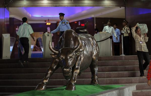 Indian security guards are stationed near a statue of a bull at the Bombay Stock Exchange building in Mumbai, India. The nations economy is plagued by inflation, budget deficits and a shrunken currency.