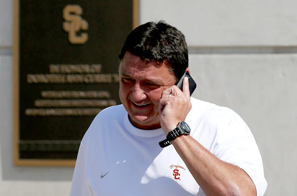 Ed Orgeron, USC's interim football coach, chats on the phone while walking to the practice field Wednesday.