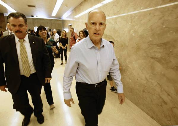 Gov. Jerry Brown walks through the Capitol