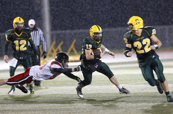 Aberdeen Roncalli's Brayden Hilton (13) out runs the diving tackle attempt of Sisseton's Nick Peterson, left, during Friday night's game at Swisher Field. Looking on for Roncalli is Zach Lundquist (12) and blocking for Hilton is Dalton Cox (22). photo by john davis taken 10/4/2013