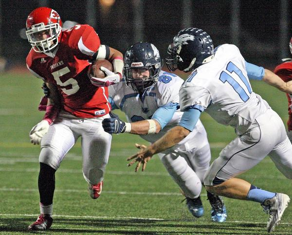 Burroughs' Javier Pineda, from left, tries to evade Crescenta Valley defenders Matt Erickson and Kevin Hello in a comeback 24-17 lead for the Indians.