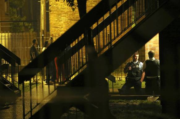 Chicago police officers guard the entrance to an apartment, the scene of a shooting during a party on the 3200 block of W. Maypole Ave. early on Oct. 5.