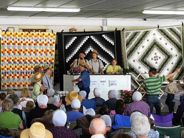 Auctions such as this recent quilt auction in Mifflinburg, Union County, are held to benefit health care and other programs in Amish communities.