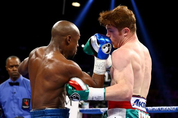 Floyd Mayweather Jr. throws a right to the head of Canelo Alvarez.