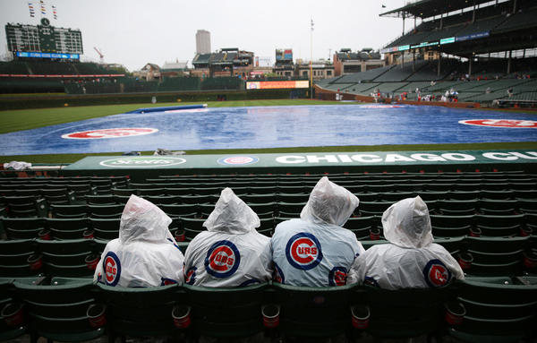 Cubs fans sit in the rain before a game against the Nationals at Wrigley Field.