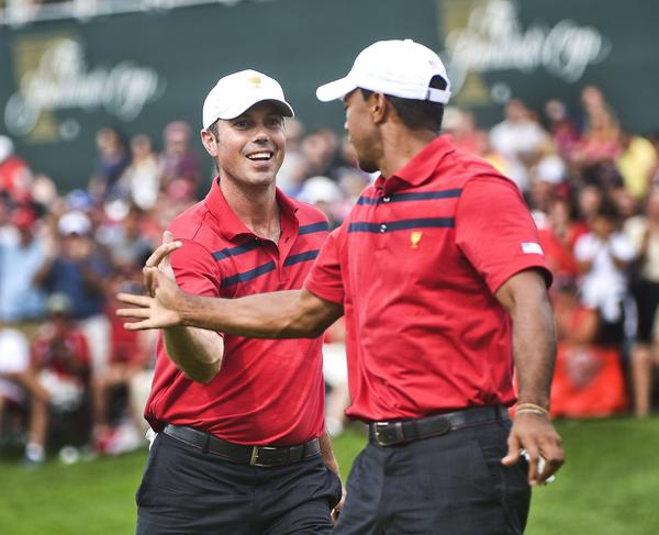 Matt Kuchar and Tiger Woods celebrate Kuchar's putt on the 14th green on Saturday.