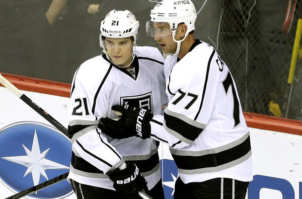 Kings forwards Matt Frattin (21) and Jeff Carter (77) celebrate after a goal by Carter against the Wild during a season-opening, 3-2 victory in Minnesota.