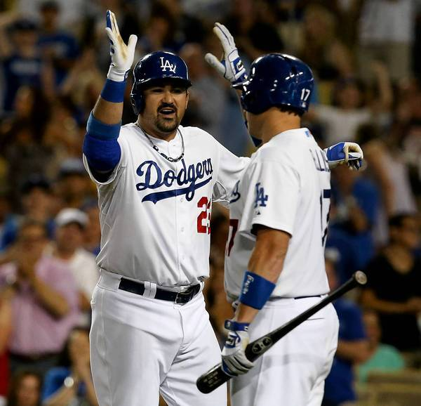 Dodgers teammates Adrian Gonzalez and Mark Ellis give each other a high five. The team's new owners have been spending big on talent and are seeing results.