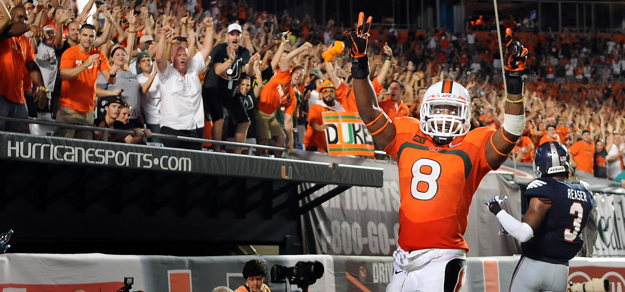 Miami's Duke Johnson celebrates his first half touchdown as Canes fans go crazy.