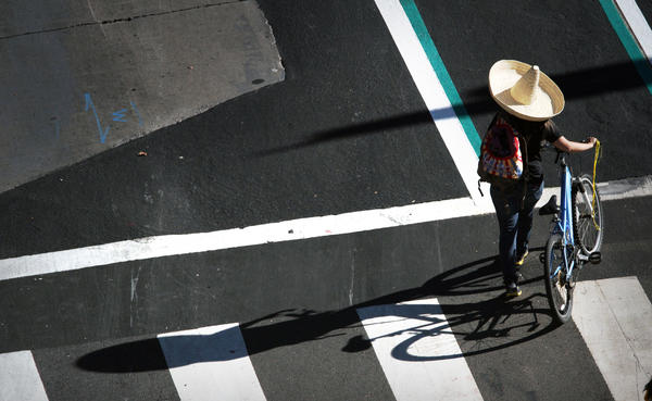 A cyclist with plenty of sun protection walks downtown before joining other CicLAvia riders at 1st and Spring streets as part of the eighth edition of the bike festival.
