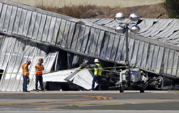 Investigators inspect the tail section of a twin-engine Cessna jet which ran off the runway and crashed into an aircraft hangar at Santa Monica Airport on Sept. 29.