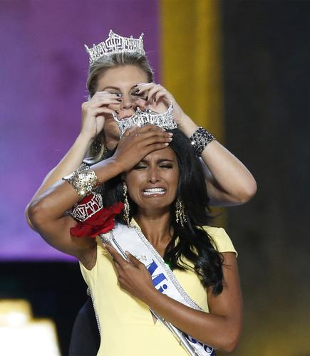 Miss America contestant, Miss New York Nina Davuluri reacts after being chosen winner of the 2014 Miss America Pageant as 2013 Miss America Mallory Hagan places a tiara on her head in Atlantic City, New Jersey, September 15, 2013. Davuluri, 24, won the 2014 Miss America Pageant on Sunday, giving the prize to Miss New York for the second year in a row.