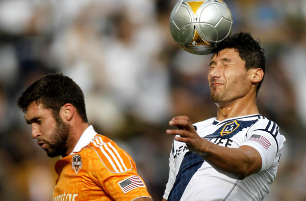 Galaxy defender Omar Gonzalez, a mainstay on the U.S. national team, heads the ball away from Dynamo forward Will Bruin.