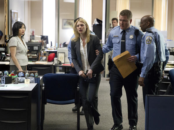 "Police officers detain CIA case officer Carrie Mathison (Claire Danes) when she tries to reveal classified information to a newspaper reporter on ""Homeland."""