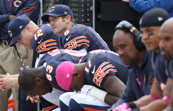 Jay Cutler (6) and his teammates watch from the bench in the third quarter.