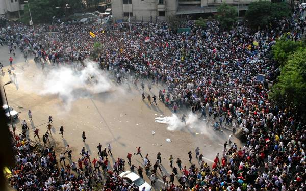 Supporters of ousted President Mohamed Morsi run for cover from tear gas during clashes with riot police in downtown Cairo.