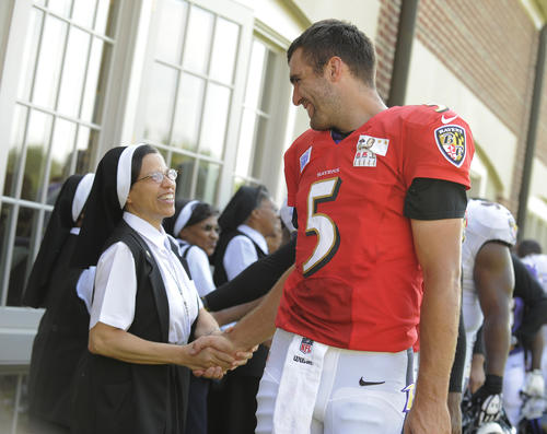 Joe Flacco is greeted by Sister Alexis Fisher of the Oblate Sisters of Providence of Catonsville after practice.