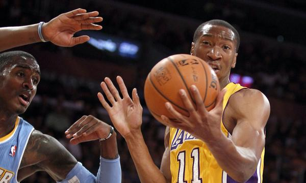 The Lakers' Wesley Johnson pulls down a rebound against Denver Nuggets forward Quincy Miller in an exhibition game.