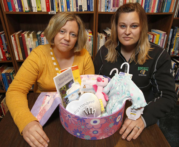 Marne Neiger, left, and Tanya Shafer, right, of Mothers of Angels, a local support group for moms who have lost infants, with one of the rememberance boxes the group gives to mothers who have experienced a loss.