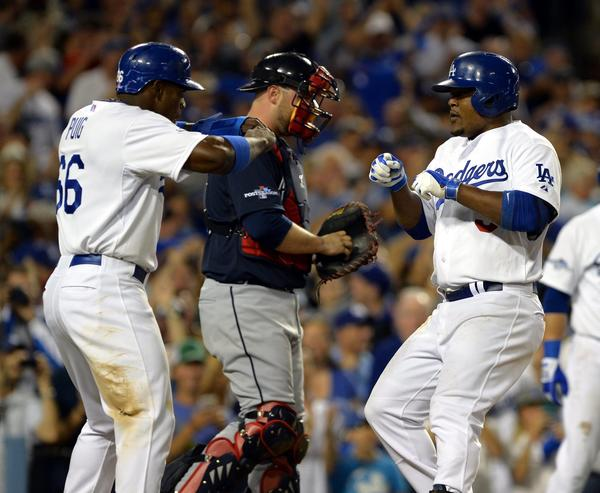 Juan Uribe is congratulated by Yasiel Puig after hitting a two-run homer against the Braves during the fourth inning.