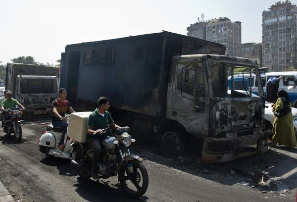 Motorcyclists pass by a burnt-out police vehicle on Monday in Cairo that was set on fire by government opponents the night before during clashes with riot police.