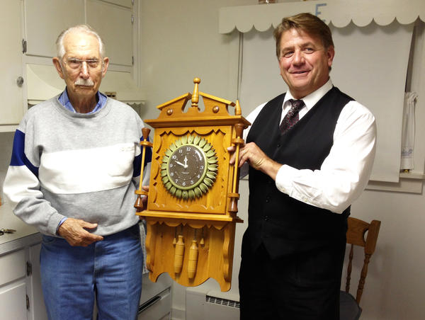 "From left: George ""Woody"" Everest of Boyne City and Ted Beck, of Rogers City hold that clock made by Everest's father, Tuesday, Oct. 1, 2013. The clock is estimated to have been made in the 1960s."
