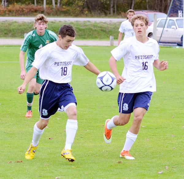Petoskey senior Ashton Walker (left) settles a free ball in front of teammate Spencer Wineman during Saturday's non-league match against Midland Dow at the Click Road Soccer Complex. The Chargers defeated the Northmen, 1-0.