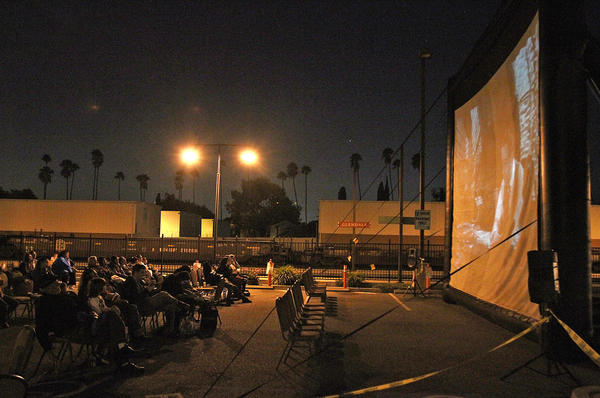 """Community members watch Billy Wilder's film noir classic """"Double Indemnity"""" as well as they can despite the light interference from the parking lot at the Glendale Metrolink Station on Thursday, Oct. 3, 2013. Glendale'sCommunity Development Department hosted a scavenger hunt, brought in food trucks, and screened the movie for the community in an effort to bring attention to the station and the area."""