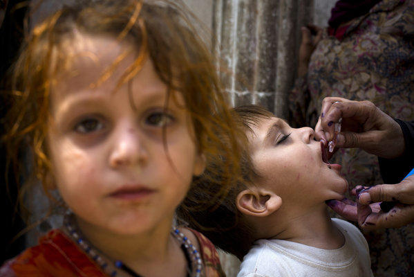 A Pakistani health worker gives a polio vaccine to a child in Rawalpindi, Pakistan, on Monday. In the city of Peshawar, a bomb exploded next to a van carrying Pakistani security guards tasked with protecting anti-polio workers, killing two.