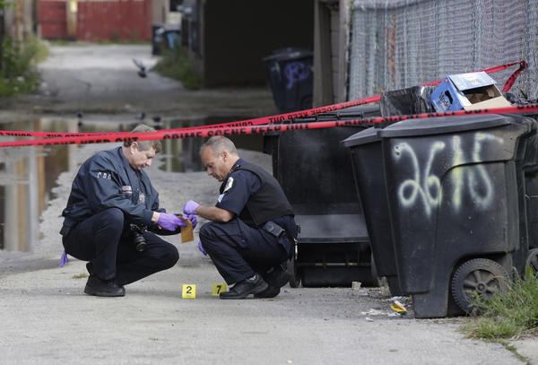 Police bag evidence in the alley near 21st Street and California Avenue in Little Village on Monday after a woman was shot.