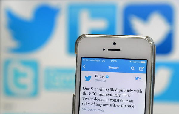 A tweet announcing Twitter's planned initial public offering (IPO) is pictured on a mobile telephone back-dropped by various twitter logos in Madrid on October 4, 2013.
