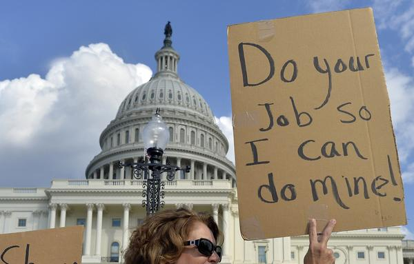 A protester holds up a sign outside the U.S. Capitol. Credit rating firm Moody's said that the government shutdown and debt ceiling crisis would not affect the country's credit rating.
