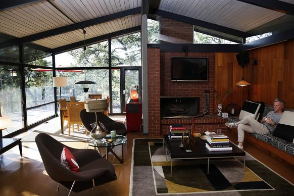 The living and dining areas of Rod Beattie's house feel suspended in treetops thanks to glass that runs from ceiling to floor on two sides, bathing the space in filtered sunshine. The clerestory windows above Beattie, on the sofa, bring in more light.