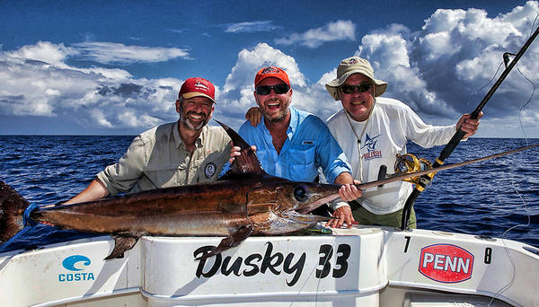 Russell Nelson, right, who passed away Saturday, was the former executive director of the Florida Marine Fisheries Commission and the chief scientist for The Billfish Foundation. Nelson and his friends from Sweden caught a swordfish two weeks ago with Capt. Bouncer Smith. Photo courtesy Dan Kipnis