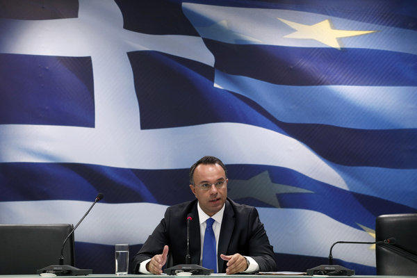Deputy Finance Minister Christos Staikouras holds a news conference in Athens. He said that the Greek economy is projected to expand 0.6% after a 4% contraction this year.