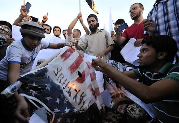 Protesters burn a replica of the American flag during a protest against the capture of Nazih al-Ragye.