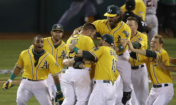 Oakland's Stephen Vogt, center left, celebrates with his teammates after driving in the winning run in the Athletics' victory over the Detroit Tigers in Game 2 of the American League division series Saturday.