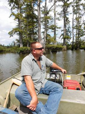 Mark Guetersloh, a biologist with the Illinois Department of Natural Resources, maneuvers his boat on the Cache River.