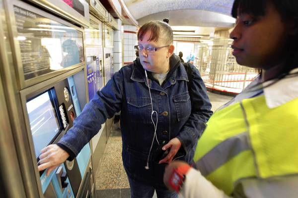 Customer service assistant Tierra Downing, right, assists Susan Guinn at a new Ventra machine at the CTA Red Line subway station at Grand Avenue and State Street. Some commuters were still are buying the old magnetic strip CTA cards, while others have made the transition to the new Ventra card.