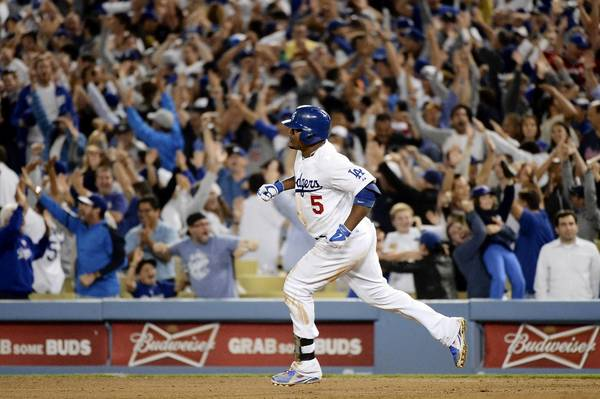 Juan Uribe of the Los Angeles Dodgers runs the bases after he hit a two-run home run in the eighth inning against the Atlanta Braves in Game Four of the National League Division Series at Dodger Stadium.