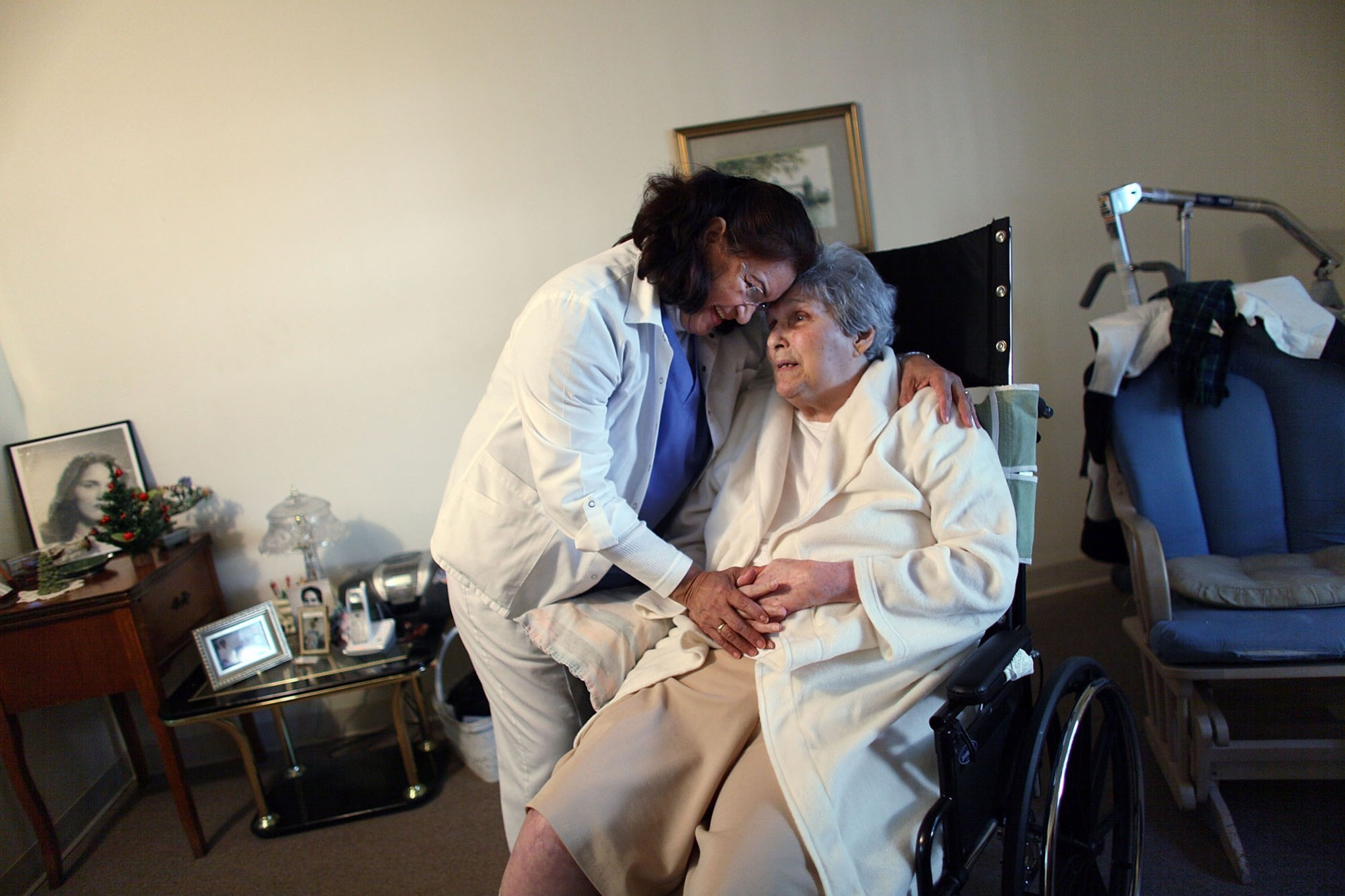 The Labor Department on Tuesday announced a rule to extend minimum wage and overtime protections to nearly 2 million direct care workers, including home health aides. Above, a home health aide working with a patient in Florida in 2010.