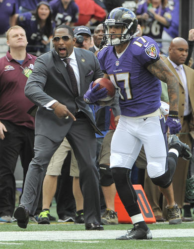 The Ravens' Tandon Doss, right, runs past former linebacker Ray Lewis as he returns a punt for a touchdown in the second quarter.